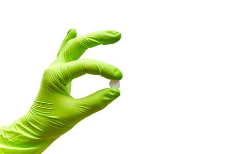 hand holds one tablet in fingers on a white background