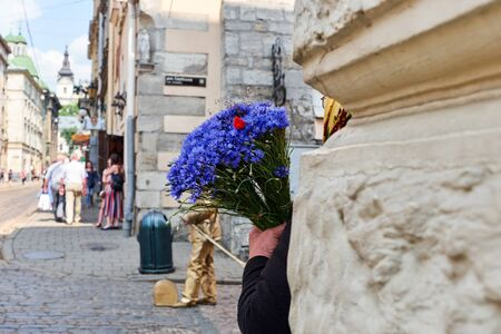 Lviv, Ukraine, June, 8, 2018. An old woman holds flowers of cornflowers in her hands in the street on a sunny day Standard-Bild