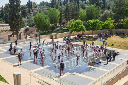 Jerusalem, Israel, June, 3, 2017. People having fun in the fountain on a hot sunny day.