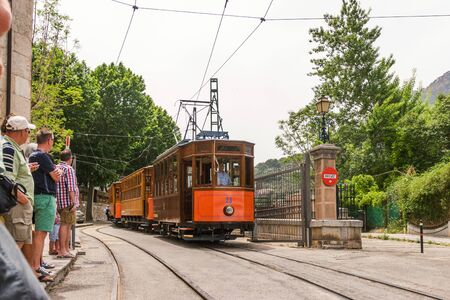 Sóller, Mallorca, May, 14, 2015. Orange tram pulls up to a stop. People are waiting for it. Standard-Bild