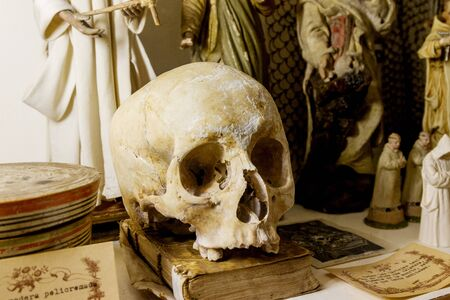 A human skull and old manuscripts lie on an old table in a museum
