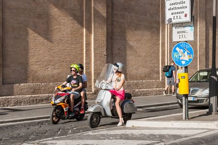 Rome, Italy, May, 18, 2015. Young people on scooters are waiting for a green traffic light on a street of Rome.