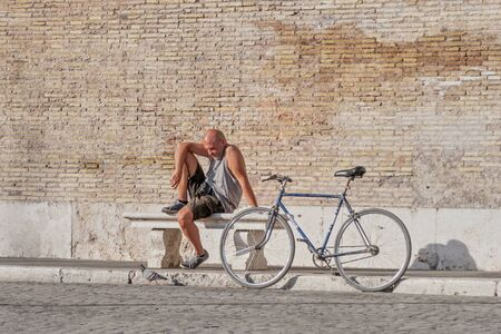 Rome, Italy, May, 18, 2015. A man sits on a bench next to a bicycle on a brick wall in Rome