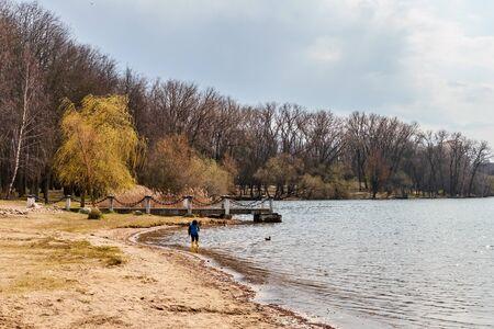 Minsk, Belarus, April, 18, 2020. Little boy runs along the lake on a sunny spring day