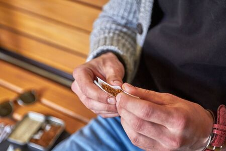 Men's hands twist a cigarette made of fine tobacco in the afternoon Standard-Bild