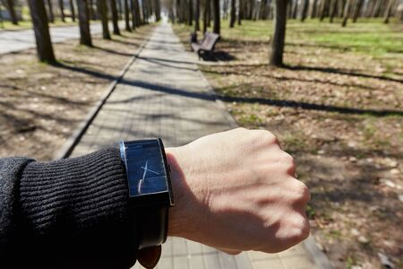 Black watch on a man s hand on the background of the track in the park on a sunny day Standard-Bild