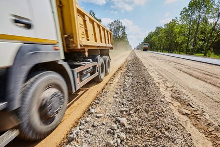 Construction of a road with rubble and sand and a truck on a sunny day Standard-Bild