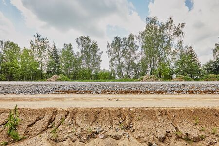 Construction of a road with rubble and sand on a sunny day Standard-Bild