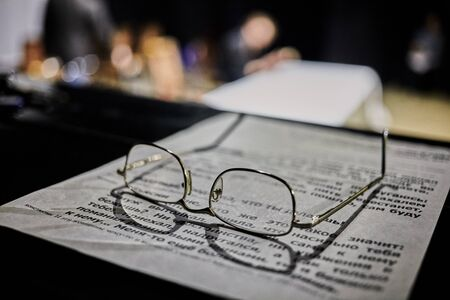 Glasses lie on paper with printed text Blurred background