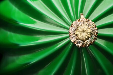 Precious ring lies on a green embossed background