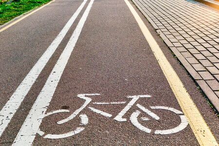 Bicycle white and yellow lanes sign and image of a bicycle with sun rays on road surface, safety zone for bike Imagens