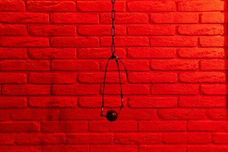 Black ball gag in mouth on red brick wall background