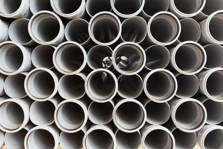Gray plastic pipes lie in rows cloudy day