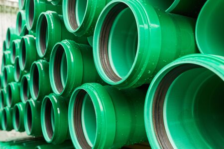 Green plastic pipes lie in rows cloudy day