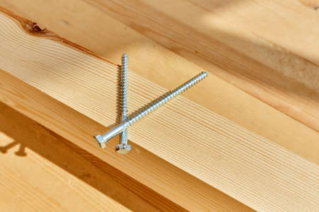 The screws lie on a wooden board sunny day