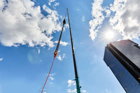 truck crane with outstretched boom on blue sky background sunny day Standard-Bild