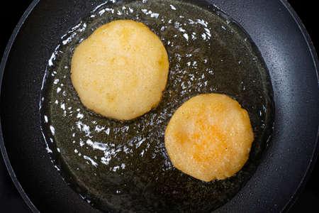 Arepas in a pan with oil. Top view. Cooking Venezuelan food. Archivio Fotografico