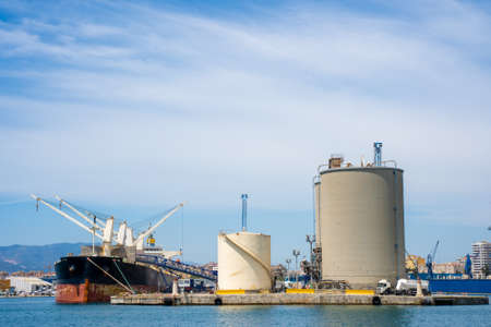 Large industrial containers in the port next to a ship with cranes and trucks Stock Photo