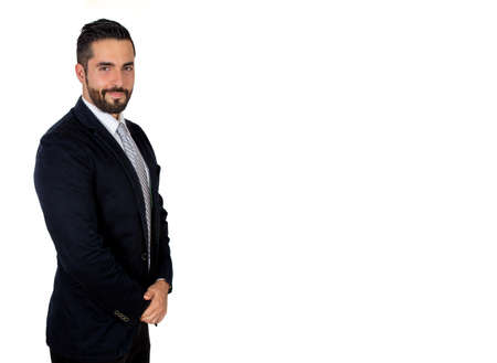 Confident handsome young bearded man in suit with copy space. Attractive stylish businessman smiling. Medium shot. White background.