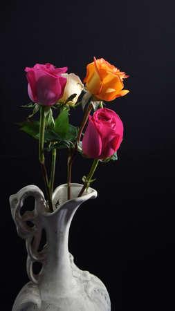 Roses in old white ceramic vase on dark background