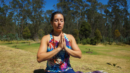 Young latin woman sitting doing yoga in the park Stock Photo