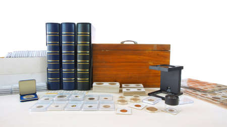Coins of different countries of the world on white table with folders and supplies background - Numismatic scene Imagens