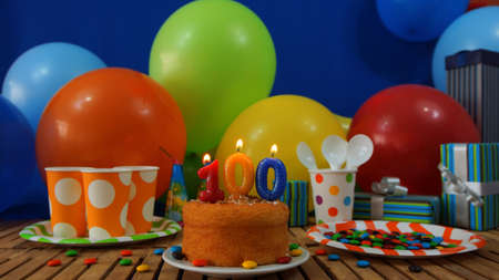 Birthday cake on rustic wooden table with background of colorful balloons, gifts, plastic cups and plastic plate with candies and blue wall in the background Stock Photo