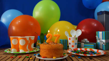 27 years old: Birthday cake on rustic wooden table with background of colorful balloons, gifts, plastic cups and plastic plate with candies and blue wall in the background Stock Photo