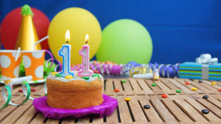 Birthday cake with candles on rustic wooden table with background of colorful balloons, gifts, plastic cups and candies with blue wall in the background. Focus is on cake 版權商用圖片