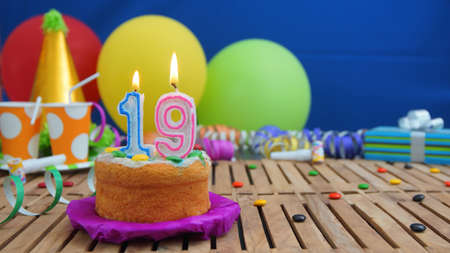 19 years old: Birthday cake with candles on rustic wooden table with background of colorful balloons, gifts, plastic cups and candies with blue wall in the background. Focus is on cake Stock Photo