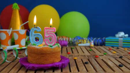 serpentinas: Torta de cumpleaños con velas en la mesa de madera rústica con el fondo de globos de colores, regalos, vasos de plástico y dulces con la pared azul en el fondo. El foco está en la torta