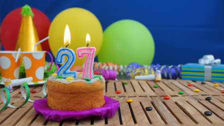 27 years old: Birthday cake with candles on rustic wooden table with background of colorful balloons, gifts, plastic cups and candies with blue wall in the background. Focus is on cake Stock Photo