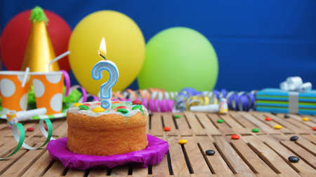 Birthday cake with candle in the shape of a question mark on rustic wooden table with background of colorful balloons, gifts, plastic cups and candies with blue wall in background. Focus is on cake Stock Photo