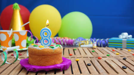 Birthday cake with candles on rustic wooden table with background of colorful balloons, gifts, plastic cups and candies with blue wall in the background. Focus is on cake Reklamní fotografie