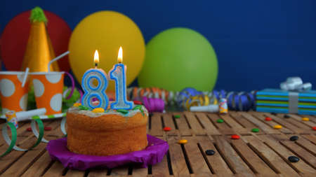 81: Birthday cake with candles on rustic wooden table with background of colorful balloons, gifts, plastic cups and candies with blue wall in the background. Focus is on cake Stock Photo