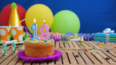 Birthday cake with candles on rustic wooden table with background of colorful balloons, gifts, plastic cups and candies with blue wall in the background. Focus is on cake Imagens