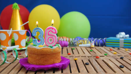 number 36: Birthday cake with candles on rustic wooden table with background of colorful balloons, gifts, plastic cups and candies with blue wall in the background. Focus is on cake Stock Photo
