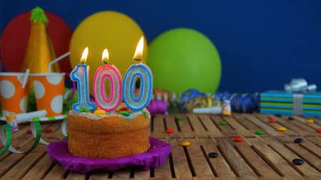 다채로운 풍선, 선물, 플라스틱 컵 및 백그라운드에서 파란색 벽 사탕의 배경 가진 소박한 나무 테이블에 촛불 생일 케이크. 초점은 케이크에있다.