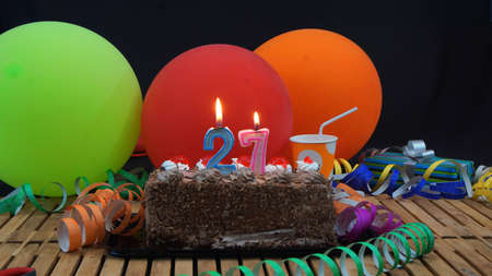 27 years old: Chocolate birthday cake with candles burning on rustic wooden table with background of colorful balloons, gifts, plastic cups and streamers with black background Stock Photo
