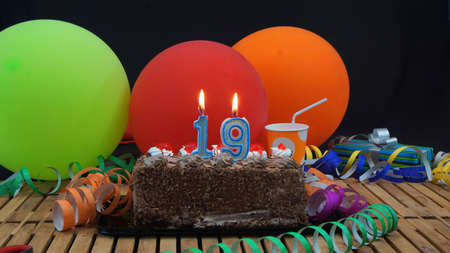 19 years old: Chocolate birthday cake with candles burning on rustic wooden table with background of colorful balloons, gifts, plastic cups and streamers with black background Stock Photo