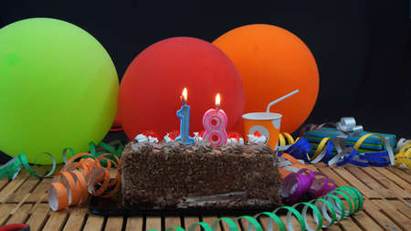 18 years old: Chocolate birthday cake with candles burning on rustic wooden table with background of colorful balloons, gifts, plastic cups and streamers with black background Stock Photo