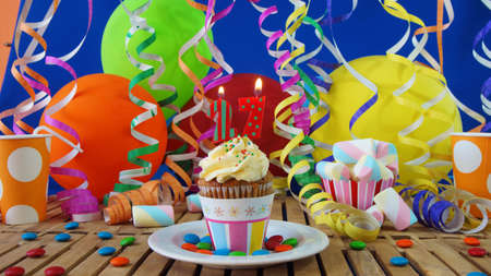27 years old: Birthday cupcake with candles burning on rustic wooden table with background of colorful balloons, plastic cups and candies with blue wall in the background