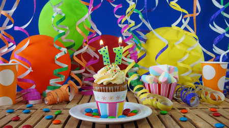 11 years old: Birthday cupcake with candles burning on rustic wooden table with background of colorful balloons, plastic cups and candies with blue wall in the background