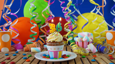 number 36: Birthday cupcake with candles burning on rustic wooden table with background of colorful balloons, plastic cups and candies with blue wall in the background