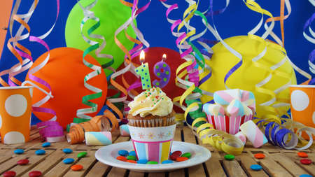 19 years old: Birthday cupcake with candles burning on rustic wooden table with background of colorful balloons, plastic cups and candies with blue wall in the background