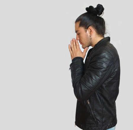 Jeune homme hispanique à l'arc en cheveux surélevé portant un t-shirt noir et une veste en cuir noir, les mains jointes en position de prière avec la tête accroupie, vu de profil Banque d'images - 78472635