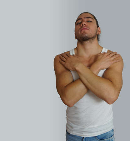 looking towards camera: Young hispanic man with raised hair done bow wearing white sleeveless t-shirt, with his hands on his chest, looking towards the camera with aggressive attitude