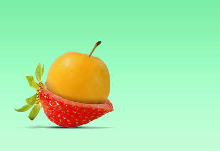 Photomontage of a greengage on a strawberry cut in half on a green background. Combination of strawberry with greengage Stock Photo