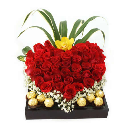 Floral gift arrangement made with red roses with chocolates inside a wooden pot on white background