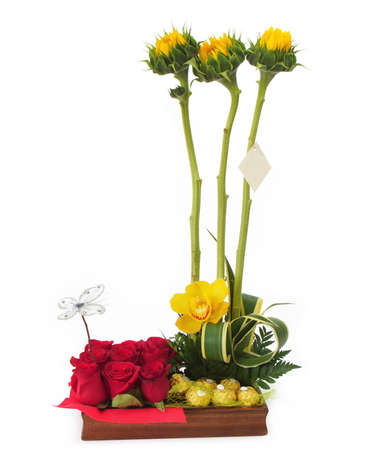 Floral gift arrangement made with red roses and sunflowers with long stems inside a wooden pot on white background